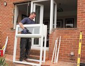 stock photo of windows doors  - A Window fitter removing old windows and doors in preparation for new plastic ones to be fitted - JPG