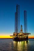 stock photo of oil derrick  - An offshore oil rig during sunset time - JPG