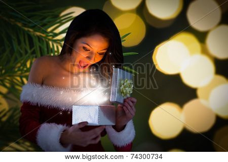 Sexy santa girl opening gift against fir tree branch with green needles