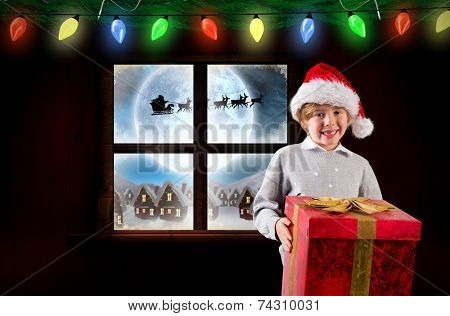 Festive boy holding gift against santa delivery presents to village