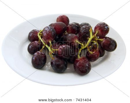 Bunch of black grapes on a white dish.