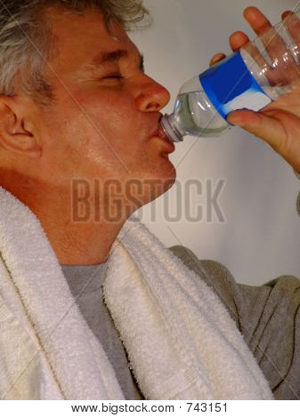 Senior Man Drinking Water after Exercise