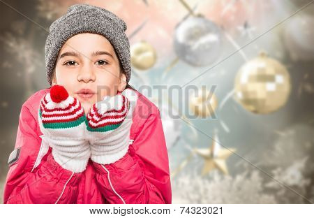 Wrapped up little girl blowing over hands against blurred christmas background