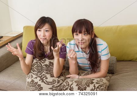 Friends watch tv and feel unhappy and confused in the living room.