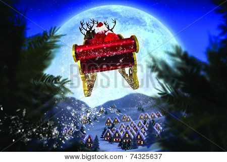 Santa flying his sleigh against christmas village under full moon