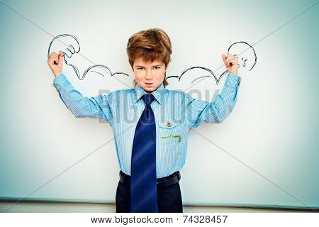 Smart boy stands by the whiteboard in a classroom expressing the power of knowledge. Educational concept. Copy space.