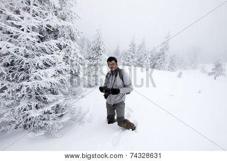 Photographer in foggy winter landscape