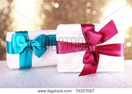 Gift boxes with vinous and blue ribbons and Christmas toy on table on shiny background