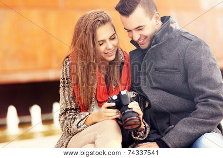 A picture of a young couple checking pictures on their camera