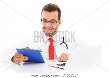 A picture of a happy doctor with laptop and documents sitting in the office