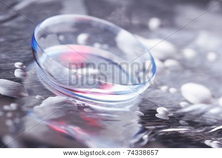 Contact lens with water drops on bright background