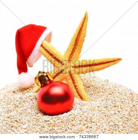 Starfish, Christmas Buable And Santa Claus Hat On The Sand