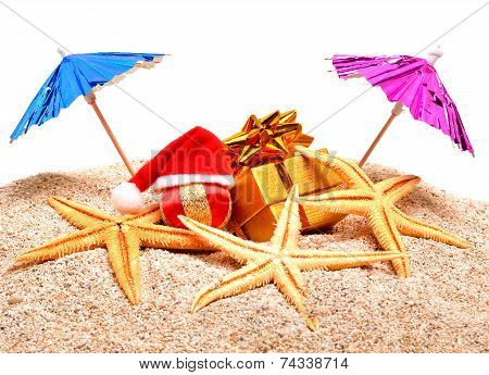 Starfish, Christmas Baubles, Gift Boxes And Coctail Umbrella On The Sand