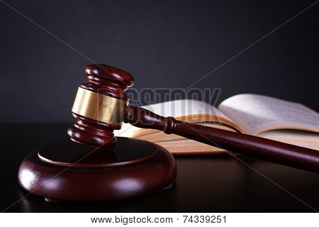 Judge's gavel and open book on dark grey background