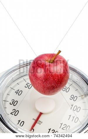 on a personal scale is an apple. symbol photo for weight loss and healthy, vitamin-rich diet.