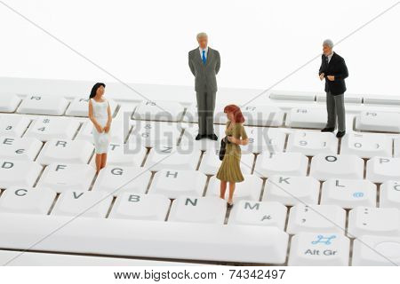 several figures of business people standing on a computer keyboard