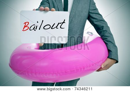 businessman with a pink swim ring showing a signboard with the text bailout written in it, depicting the financial rescue concept