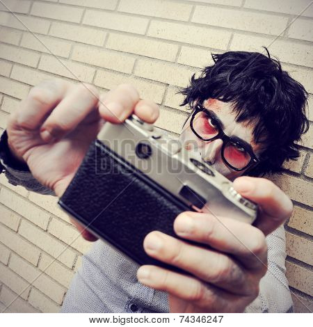 a hipster zombie taking a selfie of himself with a vintage camera, with a retro effect