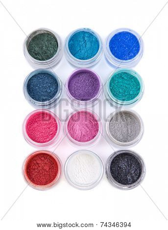 Set of colorful mineral eye shadows, top view isolated on white background