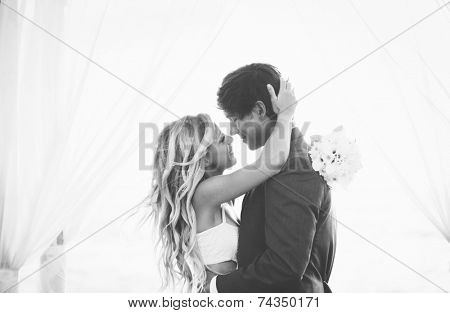 Wedding, Beautiful Romantic Bride and Groom Kissing and Embracing at Sunset. Black and White Image.