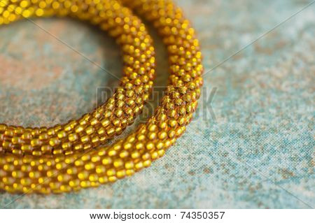 Fragment Of A Knitted Necklace From Brilliant Yellow Beads