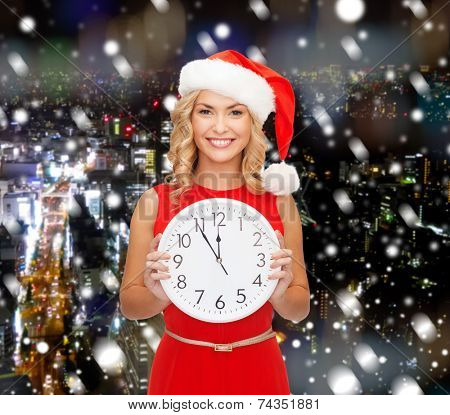 christmas, winter, holidays, time and people concept - smiling woman in santa helper hat and red dress with clock over snowy city background