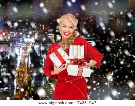 christmas, holidays, valentine's day, celebration and people concept - smiling woman in red dress with gift boxes over snowy night city background