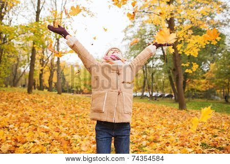 childhood, season and people concept - smiling little girl having fun in autumn park