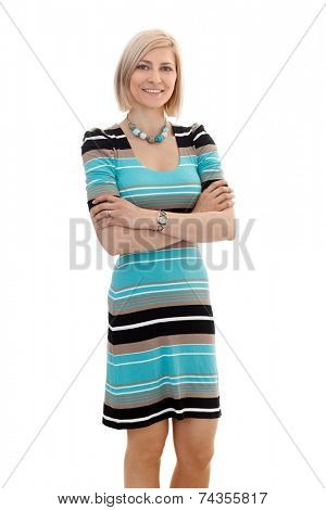 Portrait of blonde businesswoman in casual clothing standing with arms crossed, looking at camera, white background.