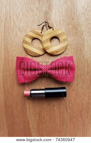 Fashion Accessories On Wooden Surface. Earrings, Bow Tie, Lipstick.