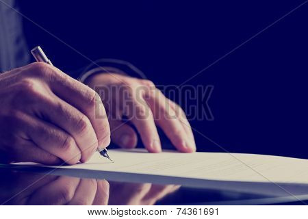 Close Up Human Hand Signing On Formal Paper