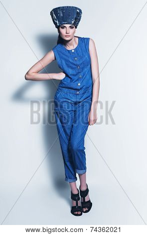 Posing Woman In Denim Jumpsuit And Hat
