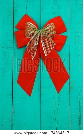 Red velvet and gold Christmas bows hanging on antique teal blue weathered wood door