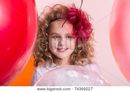 Portrait Of Happy Joyful Beautiful Girl On A Background Of The Larger Balls