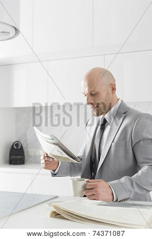 Mid adult businessman having coffee while reading newspaper in kitchen