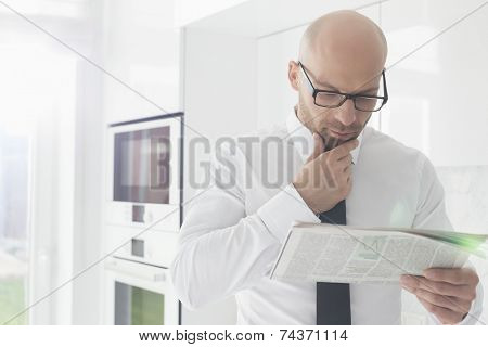 Mid adult businessman reading newspaper at home