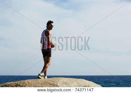 Fitness man standing on big sea rock while resting after run