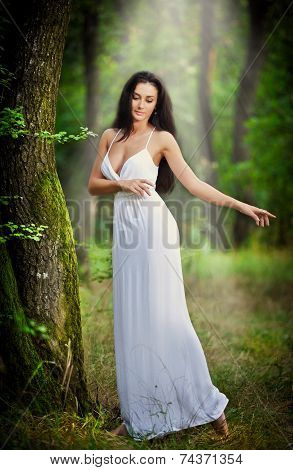 Lovely young lady wearing an elegant long white dress enjoying the beams of celestial light on her