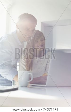 Father and daughter using laptop at home