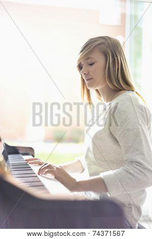 Teenage girl playing piano at home
