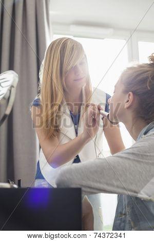 Teenage girl putting makeup on sister at home