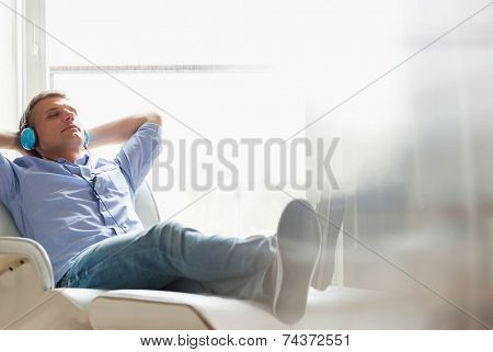 Full-length of relaxed Middle-aged man listening to music at home
