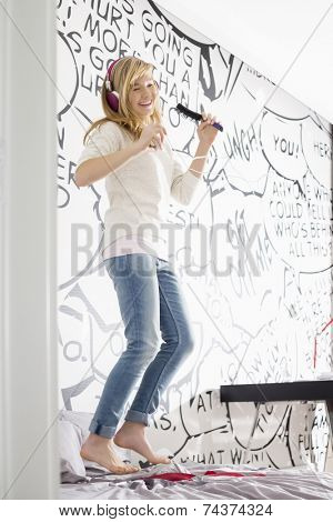 Excited girl listening music while singing into hairbrush at home