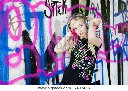 mulher com fones de ouvido no graffiti wall