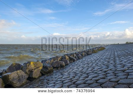 Basalt stones along a dike in a stormy sea