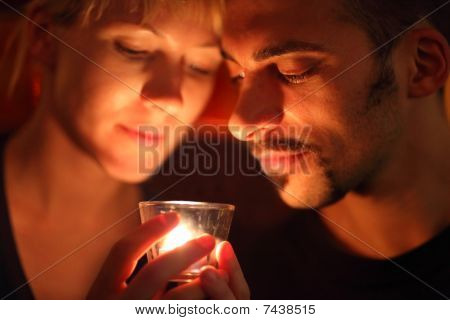man and woman keeping glass candle and looking at it.
