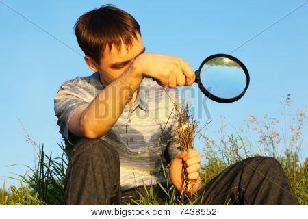 man wearing shirt and jeans with magnifier is sitting on a meadow and burning grasses
