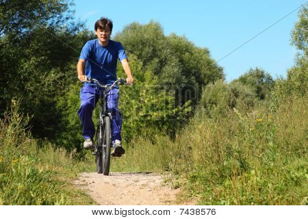 one man wearing sporty clothes is riding on a bycicle