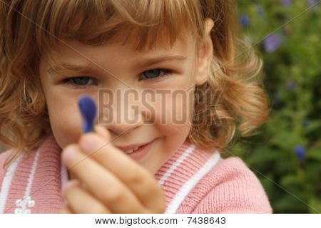 girl holding in her hand annual delphinium around flowers area