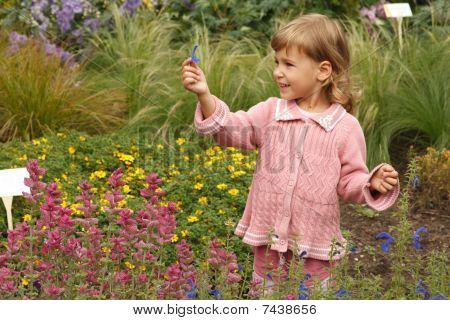 young girl holding in her hand annual delphinium pink around salvia